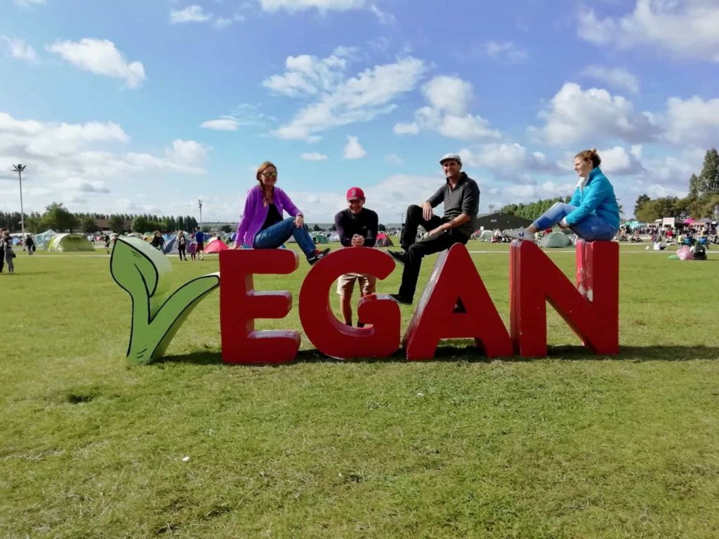 Us posing with the VEGAN sign at the Vegan Campout